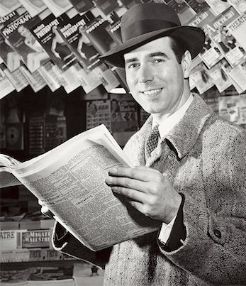 """Founder Chalmsford """"Chazz"""" Harrington reading The Sidereal Times in front of a magazine display, ca. 1928"""
